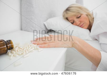 Woman lying motionless beside pills at home in her bed