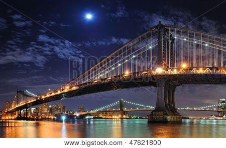 Brooklyn Bridge and Manhattan Bridge over East River at night with moon in New York City Manhattan with lights and reflections.