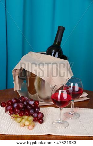 Wine and glasses on round table on cloth background