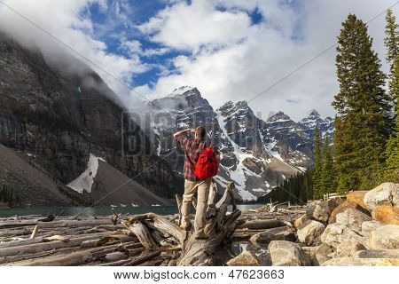 Hiking man with rucsac backpack standing on tree log by Moraine Lake looking at snow covered Rocky Mountain peaks, Banff National Park, Alberta Canada