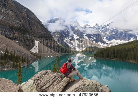 Hiking man sitting down with rucksack backpack standing on tree log by Moraine Lake looking at snow covered Rocky Mountain peaks, Banff National Park, Alberta Canada