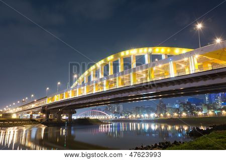 City night scene with illuminated bridge over river in Taipei, Taiwan, Asia. The bridge was named MacArthur Bridge No. 1.