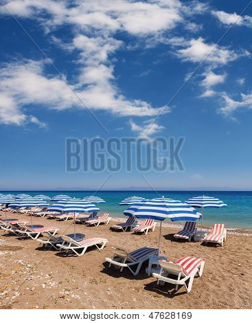 Beach With Umbrellas And Chairs Under The Sun And  Blue Sky