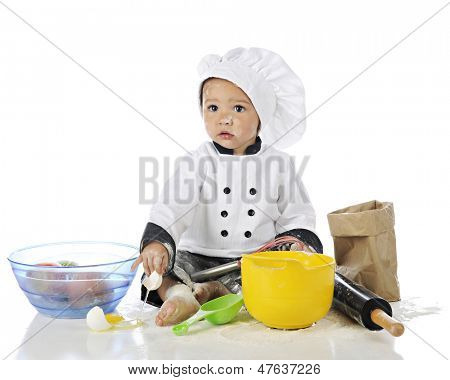 An adorable baby baker looking forlorn in his chef's outfit after breaking an egg.  On a white background.