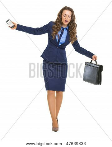 Concerned Business Woman With Briefcase And Cell Phone Balancing