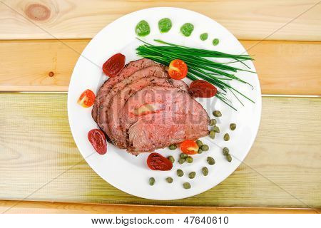 roasted meat served on white dish with capers over wood