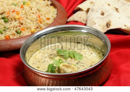A old beaten copper serving bowl with homemade fish in green curry sauce, vegetable pilau rice on a terracotta plate and a pile of chappati indian flat breads.