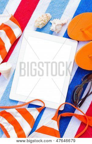 orange sandals and swimming siut on sand