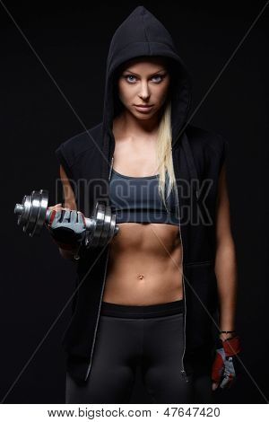 Athletic girl in a hood with dumbbell