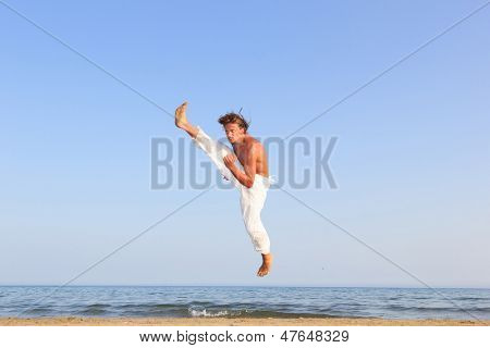 Young adult man  practicing a Kata on the beach on a sunny day