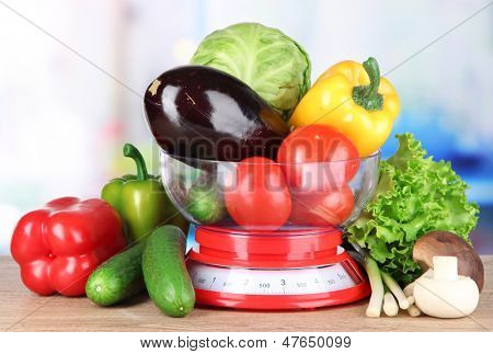 Fresh vegetables in scales on table in kitchen