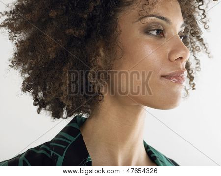 Closeup of a young afro woman with curly hair against white background