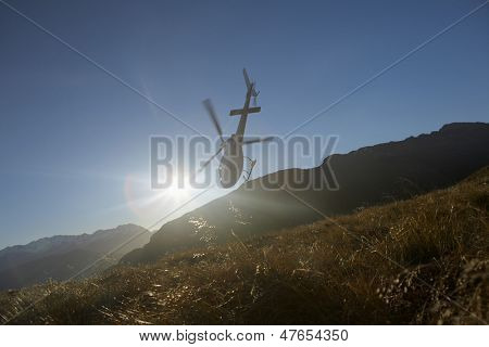 Low angle view of a helicopter flying over hills in front of the sun