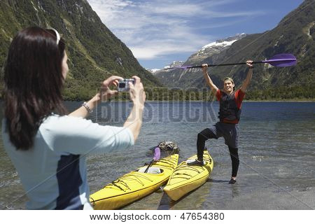 Woman taking picture of man raising kayak oar over head on shore of mountain lake