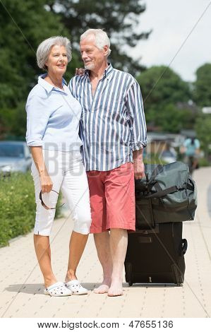 Smiling senior couple with luggage