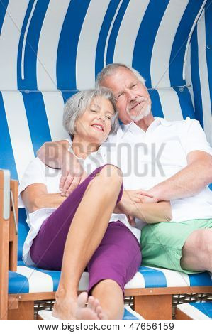 Happy and smiling senior couple in a beach chair
