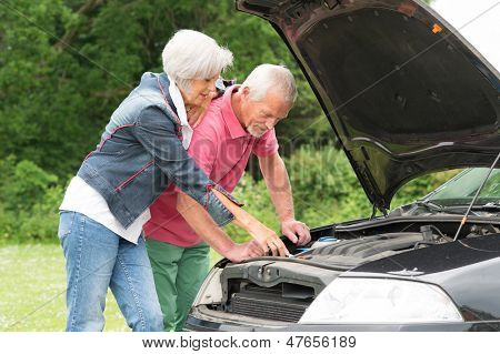 Senior couple standing together at a broken car