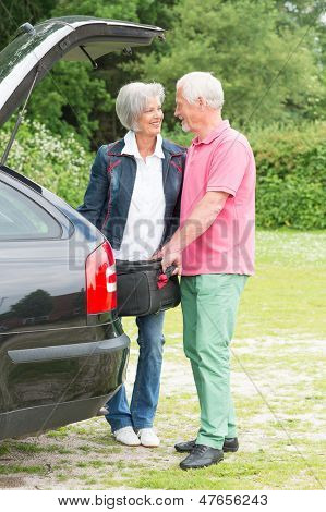 Senior couple with luggage at a black car
