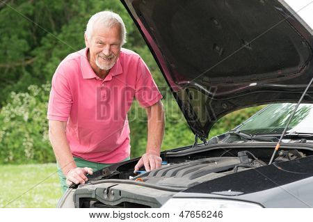Active senior man working at car