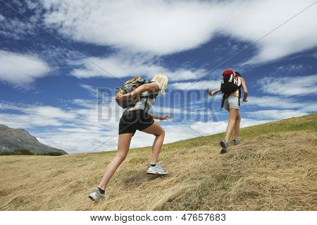 Rear view of two women running up hill against cloudy sky
