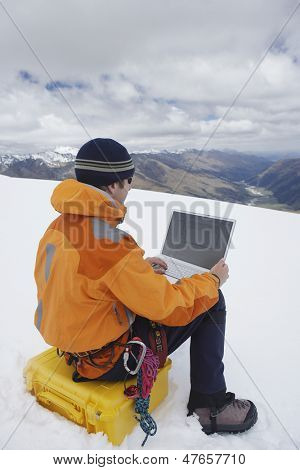 Rear view of a male hiker using laptop on snowy mountain landscape
