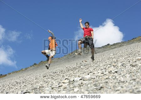 Low angle view of two men jumping down scree field
