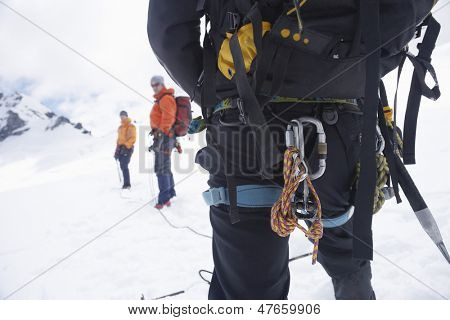Rear view of a hiker with backpack and safety rope while two friends ahead on snowy landscape