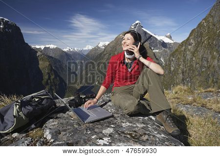 Young woman using laptop and walkie talkie on boulder against mountains
