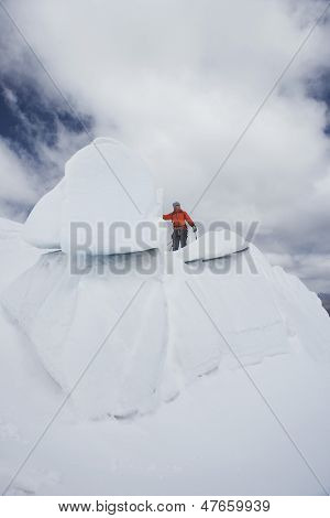Low angle view of a male hiker standing on top of ice formation against clouds