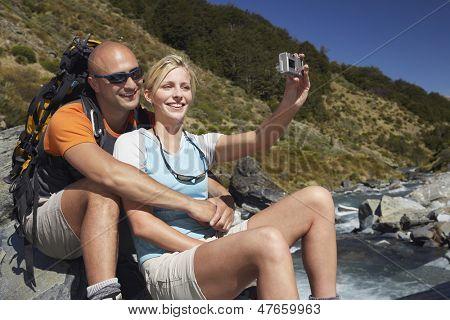 Mann umarmt Frau, wie sie ihr Bild vom Fluss im Wald nimmt