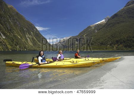 Side view of three young people kayaking in the lake with mountains in background
