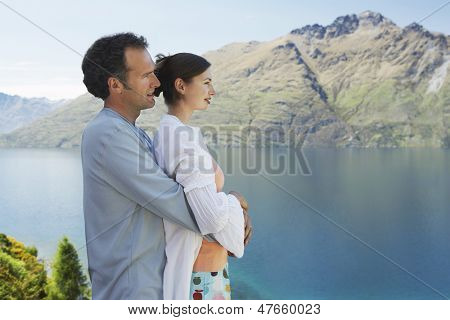 Side view of a man embracing woman from behind while looking at the mountain lake