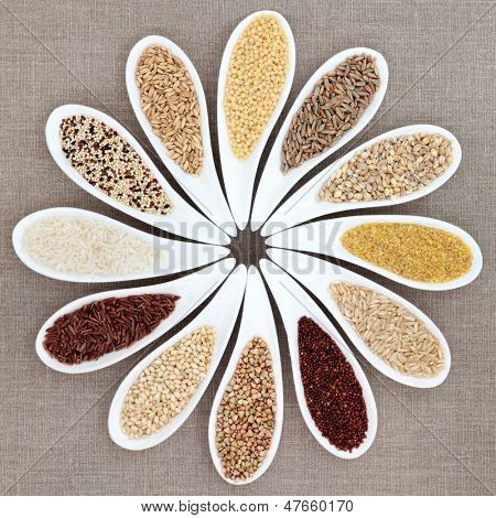 Grain food selection in white porcelain dishes over hessian background.