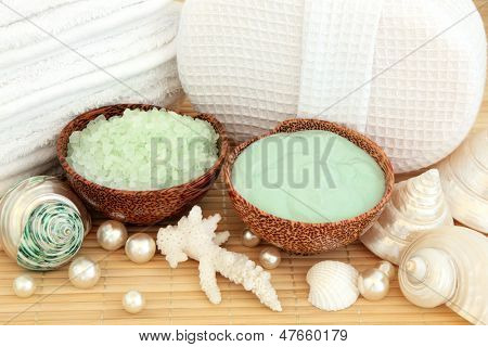 Skincare products of moisturising cream and bath salts with bathroom accessories, sea shells and pearls over bamboo.