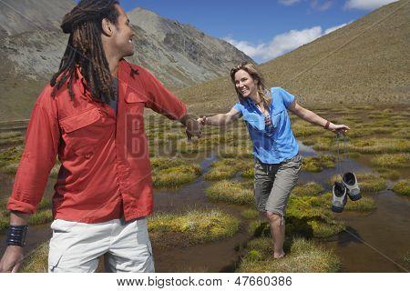 Mann helfen fröhlich Frau Wade durch Teich während sie Schuhe trägt