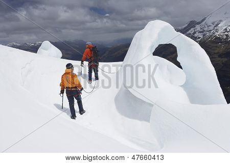 Rear view of two hikers going past ice formation in mountains