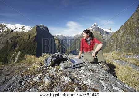 Young woman sitting with laptop on boulder against mountains