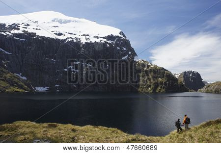 Two hikers looking at peaceful lake with mountain in background