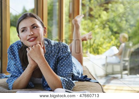 Young woman with hands clasped to chin lying by windows overlooking forest