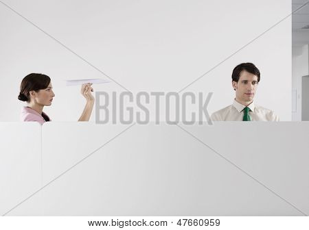 Female executive throwing a paper aeroplane at male colleague in the office