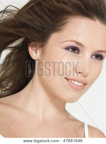 Closeup of a beautiful smiling young woman with wind swept hair