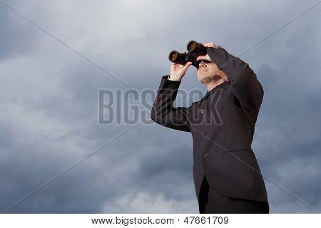 Full length of businessman looking through binoculars against cloudy sky