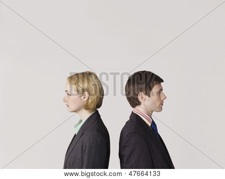 Side view of two business people standing back to back on gray background