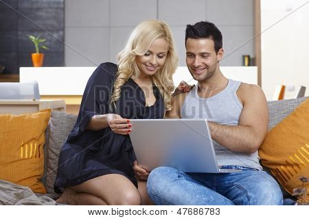 Young couple using laptop computer, sitting on couch, woman in dressing gown.