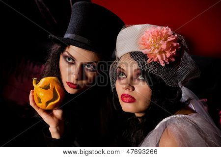 Halloween concept: sexy ladies vampire with halloween pumpkins over red background