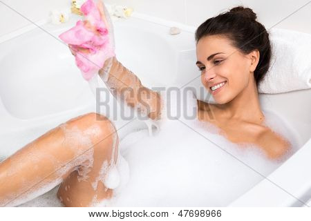 young woman takes bubble bath
