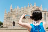 picture of memento  - Woman tourist in Mallorca taking photographs of landmark buildings while enjoying the adventure of a a summer vacation in Europe view from behind - JPG