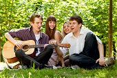 picture of singing  - Four happy smiling teenage friends singing by guitar - JPG