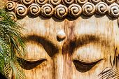 image of siddhartha  - detail of a wooden zen sculpture in a zen garden - JPG