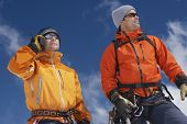Two male mountain climbers standing against sky with one using walkie talkie